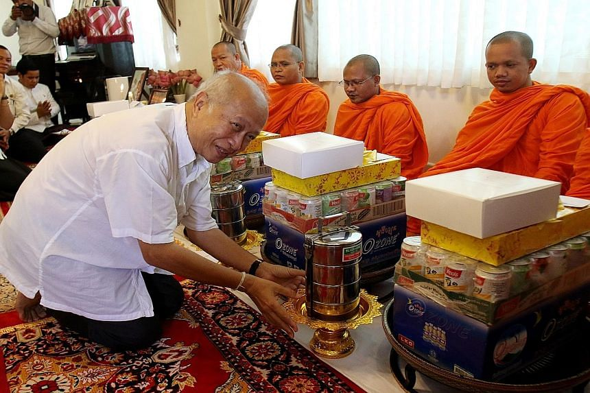 Cambodian Prince Norodom Ranariddh, president of the royalist Funcinpec Party, offering food to monks during the third anniversary of the death of King Norodom Sihanouk in Phnom Penh, Cambodia, yesterday.