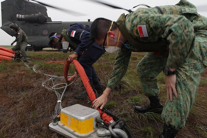 Members of the combined Singapore Armed Forces-Singapore Civil Defence Force firefighting assistance team rigging a 5,000-litre heli-bucket to a CH-47D Chinook helicopter before a water-bombing operation in South Sumatra. The team was deployed to the