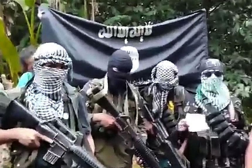 This undated YouTube video grab shows gunmen standing behind the four hostages (not pictured) who were kidnapped last month from a resort on Samal Island, off Davao city, in the Philippines.