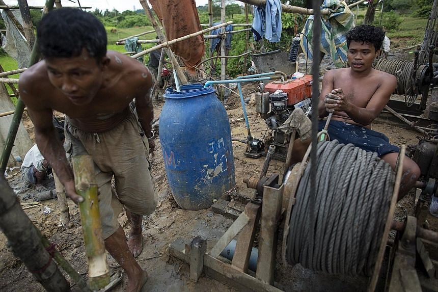 Men extracting crude oil by hand at Yaynan Taung (Oil Mountain) in Kyaukpyu township, Myanmar. China is taking steps to protect strategic investments in Myanmar ahead of an unpredictable election next month. The fishing town of Kyaukpyu is at the hea