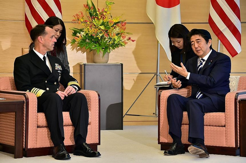 US Chief of Naval Operations John Richardson with Japanese Premier Shinzo Abe during a meeting at Mr Abe's office in Tokyo yesterday. Admiral Richardson is in Japan at the start of a 12-day trip around Asia and Europe.