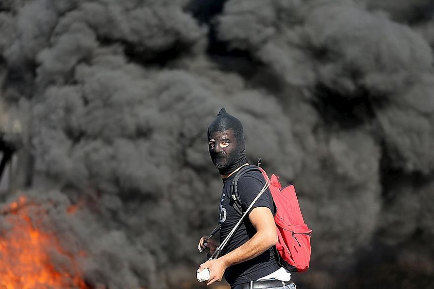 A fire rages behind a Palestinian protester during clashes with Israeli troops near the West Bank city of Ramallah on Wednesday. There has been an upsurge of unrest since Oct 1 and officials have called for Israelis to be vigilant. They also urge hol