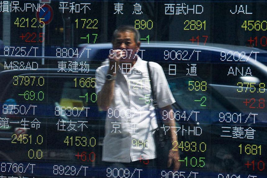 A man looking at stock prices displayed at a board showing market indices in Tokyo on July 28, 2015.