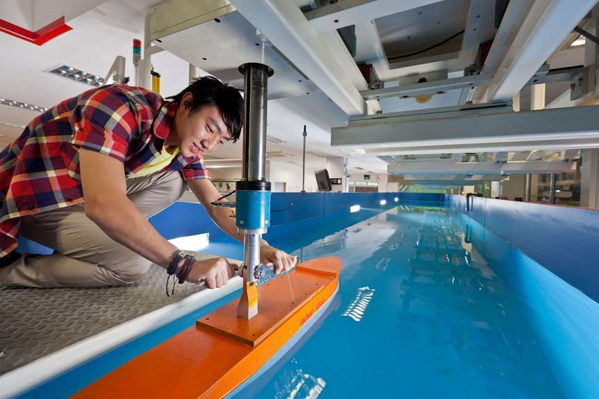 A student from Ngee Ann Polytechnic's Marine and Offshore Technology diploma course fixing a ship prototype in the poly's towing tank.