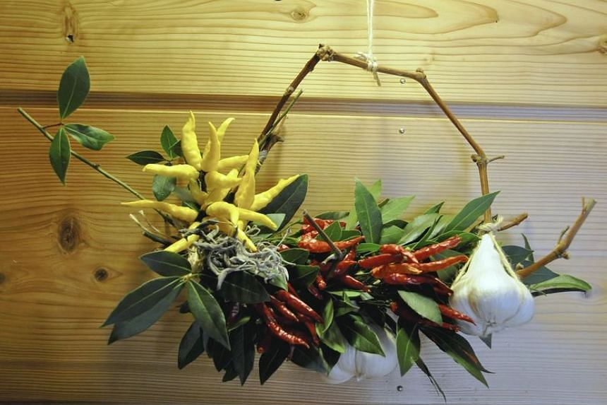 A wreath of red and yellow chili peppers and bay leaves.