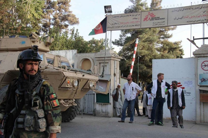 MSF staff and Afghan military personnel stand outside the entrance to the MSF hospital in Kunduz.