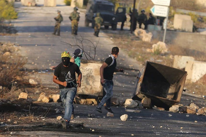 Palestinian protestors clash with Israeli troops near the Jewish settlement of Beit El, near the West Bank city of Ramallah Oct 15, 2015.