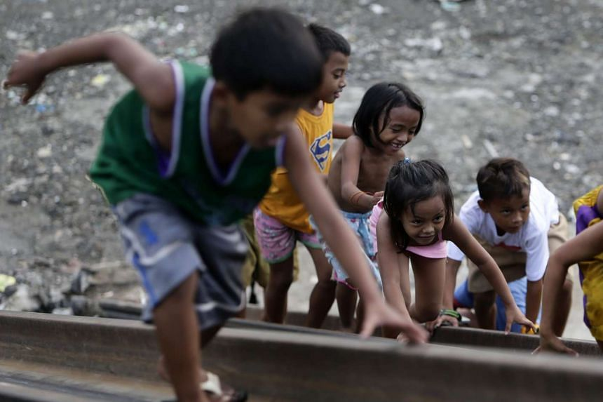 Filipino children play at a flood control project at a river in Paranaque city, south of Manila, Philippines.