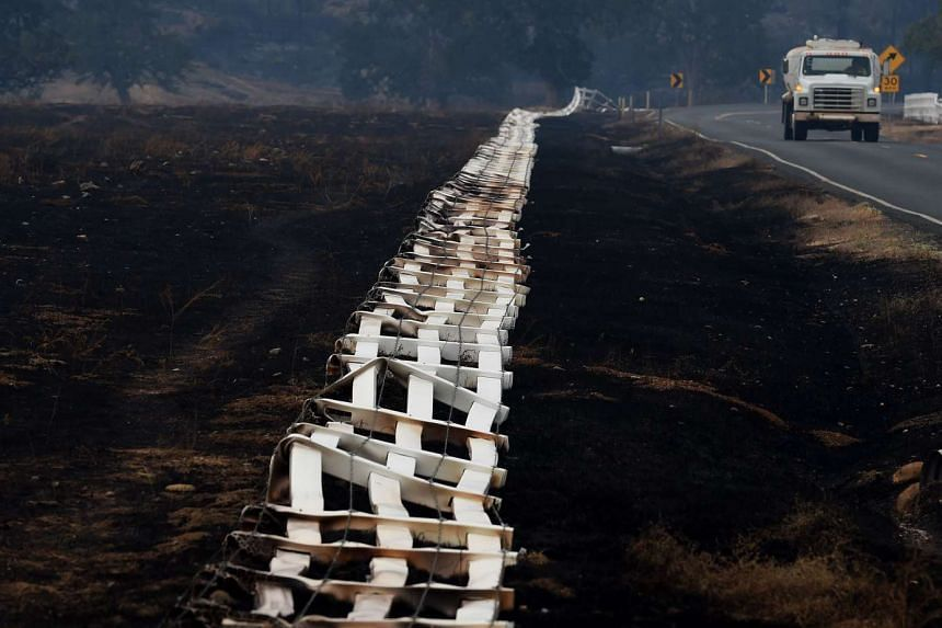 """A burnt fence lies on its side as firefighters continue to battle the """"Valley Fire"""" in the town of Middletown, California on Sept 15, 2015. Wildfires sweeping across California are threatening the US state's famed Sequoia trees, with firefighters scr"""