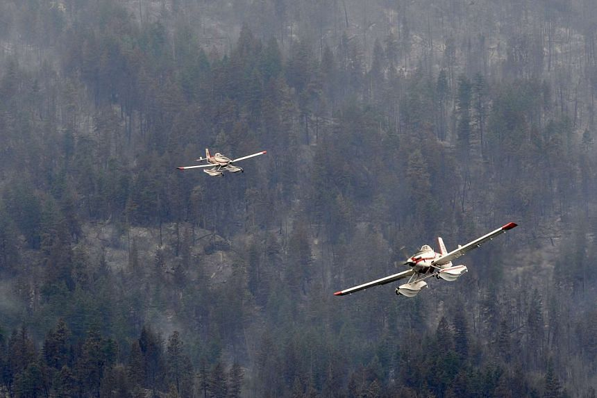 A pair of single engine water bombers return to Okanagan Lake for more water during efforts to fight the Westside Road wildfire in Kelowna, British Columbia, Canada, on July 23, 2015.