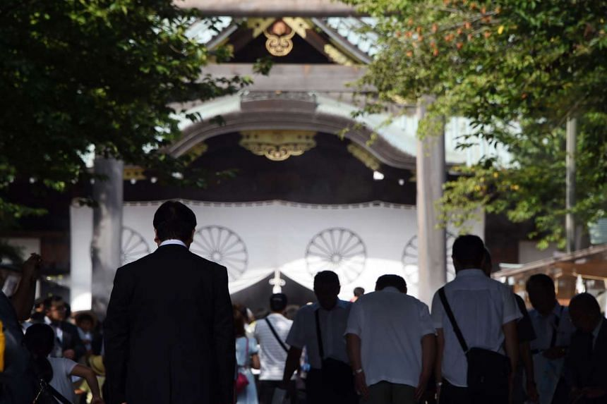 People bowing at the entrance of the controversial Yasukuni shrine in Tokyo on Aug 15, 2015.