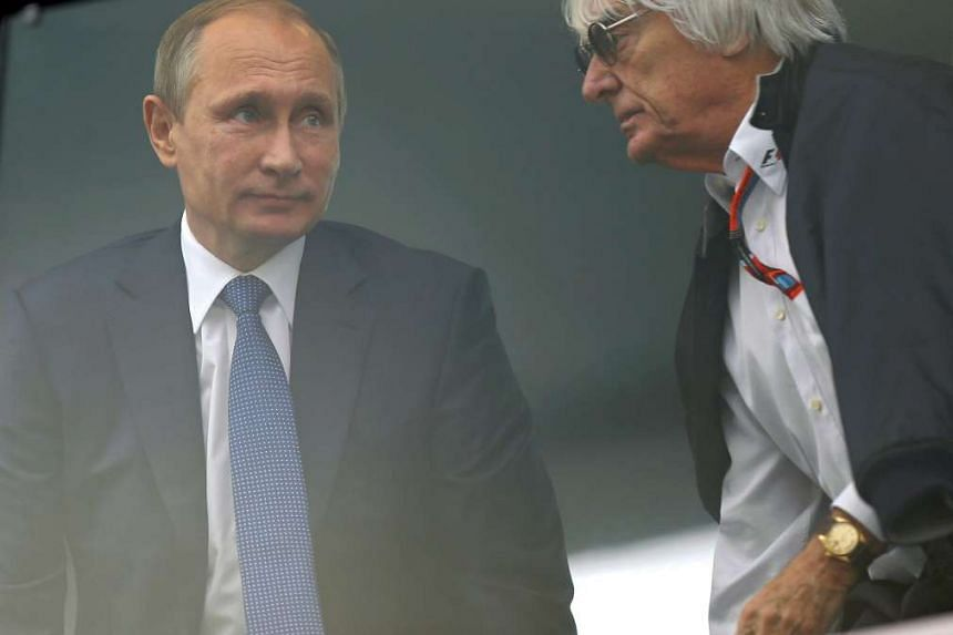 Russian President Vladimir Putin (left) and Formula One boss Bernie Ecclestone (right) take their seats during the 2015 Formula One Grand Prix of Russia at the Sochi Autodrom circuit, in Sochi, Russia, on Oct 11, 2015.
