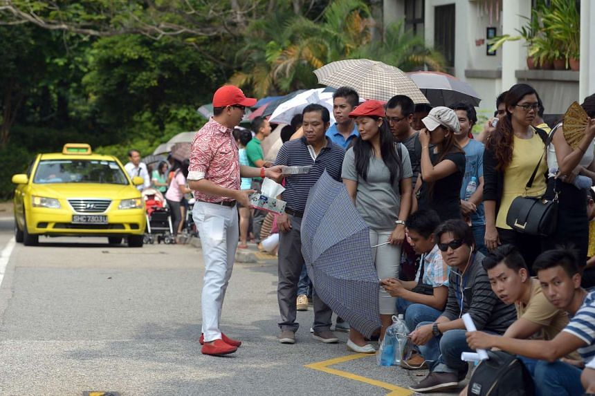 A man giving out sweets and tissue paper to others in the queue on Oct 15.