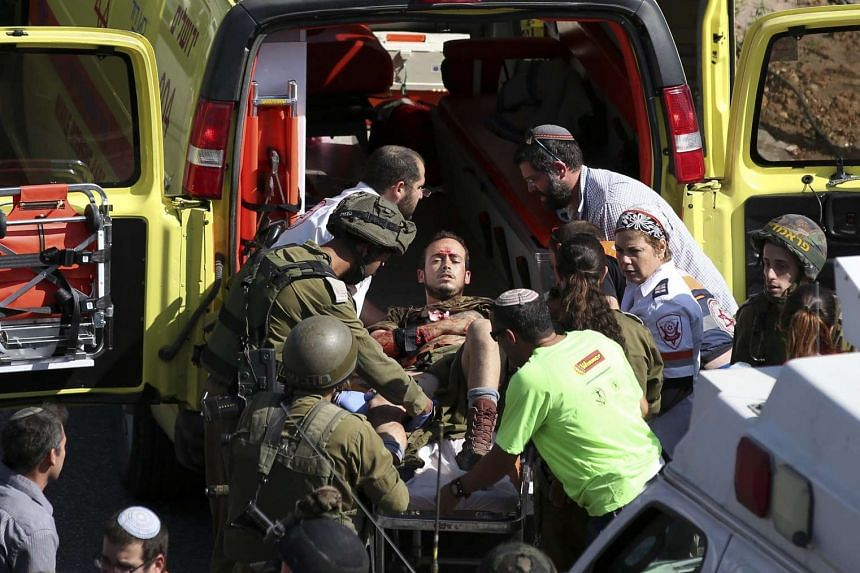 Israeli soldiers lift a wounded comrade into an ambulance car after he was stabbed by a Palestinian protester, who was shot and killed, in the West Bank city of Hebron, on Oct 16, 2015. The attacker pretending to be a local news photographer was wear