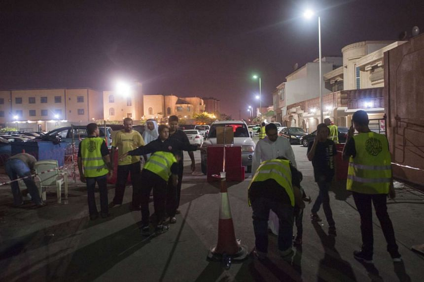 Saudi Shi'ite worshipers are frisked by security as they make their way to a hussainiya, a Shi'ite hall used for commemorations, in Qatif on Oct 16.