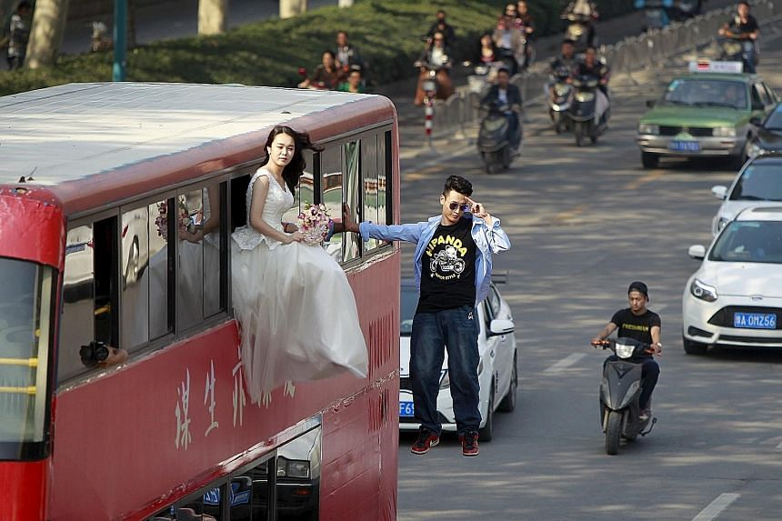 Chinese magician Lei Xin suspended outside a double-deck bus next to a woman in a wedding gown during a magic performance in Zhengzhou, Henan province, on Thursday. The performance, organised by Lei and his friends, was aimed at promoting a healthier