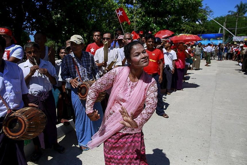 Myanmar's ethnic Rakhine people dancing to welcome opposition leader Aung San Suu Kyi during her campaign rally for the upcoming general election in Thandwe yesterday. Ms Suu Kyi has opted to skip state capital Sittwe and other more restive areas of
