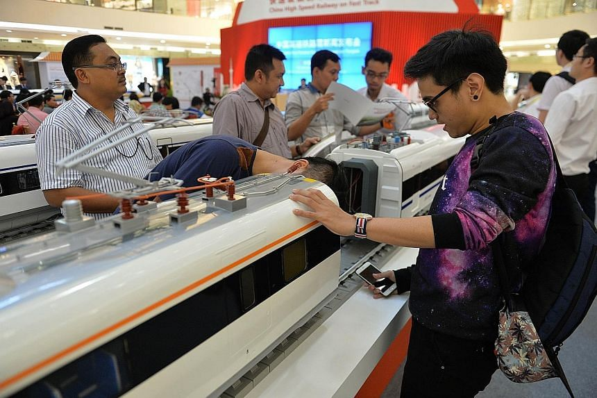 Visitors looking at models of Chinese-made bullet trains on exhibition at a shopping mall in Jakarta. Chinese and Indonesian state-owned companies will jointly build the first high-speed railway in Indonesia.
