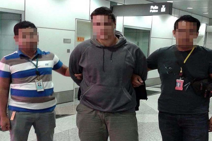 Malaysian police said they have arrested a man (centre), identified by the US as Kosovo citizen Ardit Ferizi, who is wanted for allegedly stealing data related to more than 1,000 US military and government personnel and providing the information to I