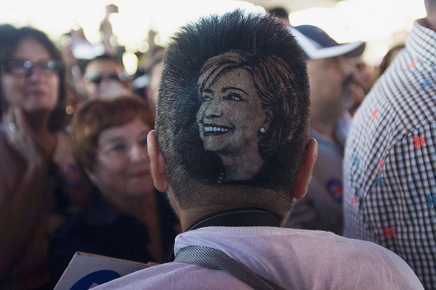 """A supporter of Mrs Hillary Clinton with an image of the presidential contender imprinted on her hair at a """"Latinos for Hillary"""" presidential campaign rally in San Antonio, Texas, on Thursday. The rally was the first of a series of events designed to"""