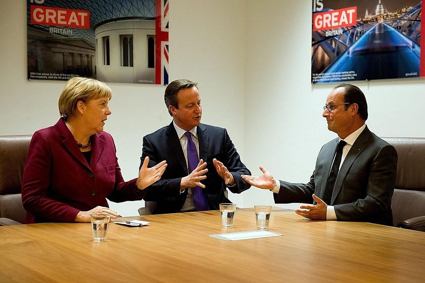 Mr David Cameron (centre) with German Chancellor Angela Merkel and French President Francois Hollande at the European Union summit in Belgium on Thursday.