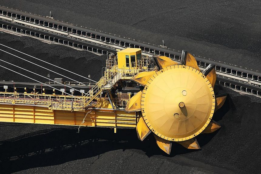 (Top) A stacker reclaimer at the Newcastle Coal Terminal in Australia. The global economic slowdown is exacerbating a coal glut that has driven prices for the fuel to the lowest level in eight years, according to Glencore. Its CEO Ivan Glasenberg (ab