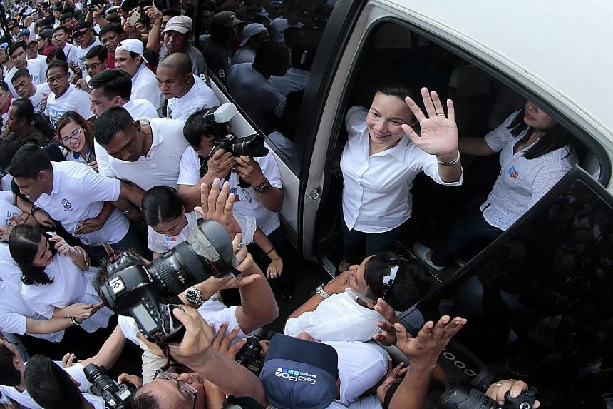 Leading contender Senator Grace Poe (top, right) waving to supporters after filing her certificate of candidacy in Manila on Thursday. The presidential election is scheduled for May next year.