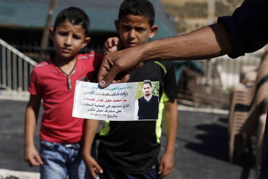 The father of Bahaa Allyan, who was killed by Israeli police after shooting three Israelis on a bus in Jerusalem, holds a photo of his son at his home in the Palestinian neighbourhood of Jabal Mukaber on Oct 15.