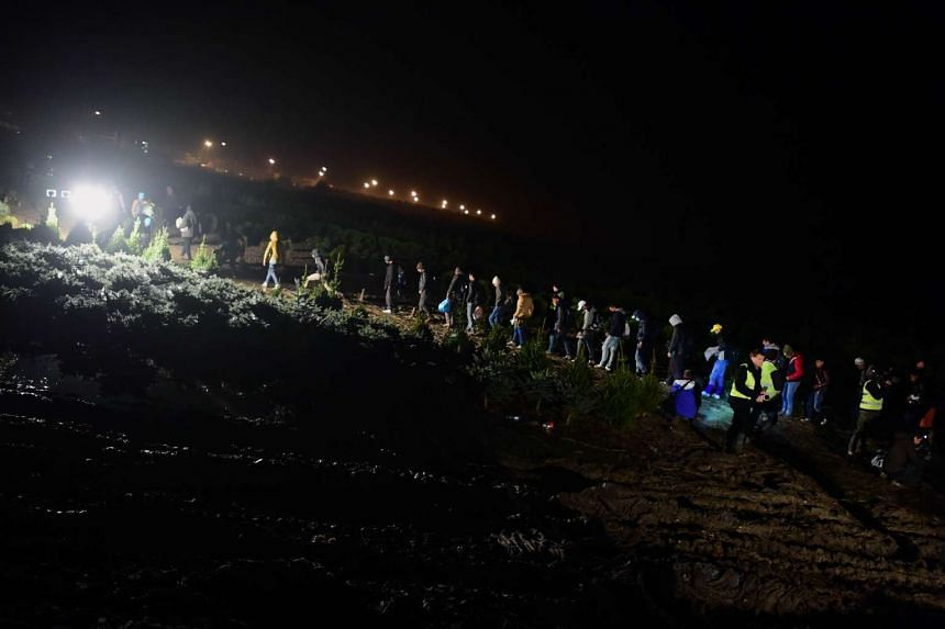 A group of migrants cross the border before Hungarian soldiers closed the border between Hungary and Croatia in Zakany on Oct 16, 2015.