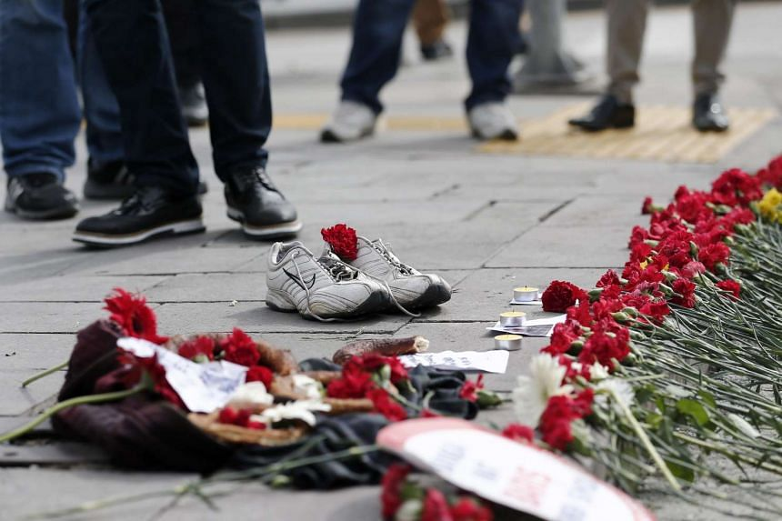 People place flowers and shoes on the ground in tribute to victims of a twin bombing attack, in Ankara, Turkey, on Oct 12, 2015.