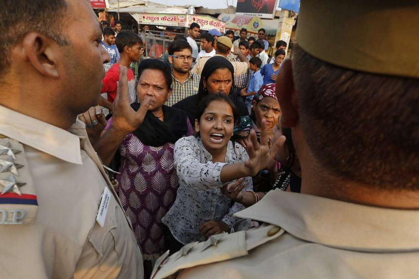 Indian women shout at police officers near the house of a two-and-a-half-year-old girl who was allegedly raped, in New Delhi, India, on Oct 17, 2015.