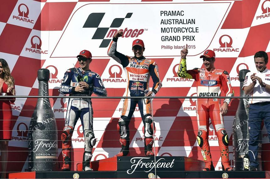 Repsol Honda Team rider Marc Marquez (centre) celebrating his victory at the MotoGP Australian Grand Prix, with second-placed Movistar Yamaha rider Jorge Lorenzo (second left) and third-placed Ducati rider Andrea Iannone (second right) on Oct 18, 201