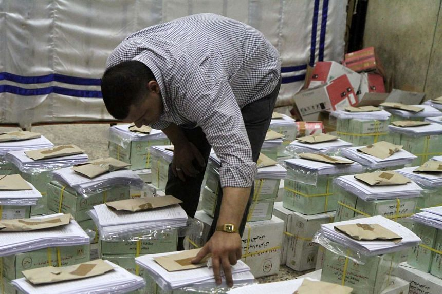 An Egyptian official inspects boxes containing ballot cards for the Egyptian parliamentary elections in the Giza district of Cairo on Oct 17, 2015.