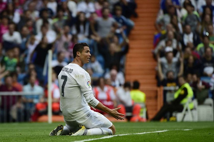 Real Madrid's Portuguese forward Cristiano Ronaldo gestures as he kneels on the field during the Spanish league football match Real Madrid CF vs Levante UD at the Santiago Bernabeu stadium in Madrid on Oct 17, 2015.