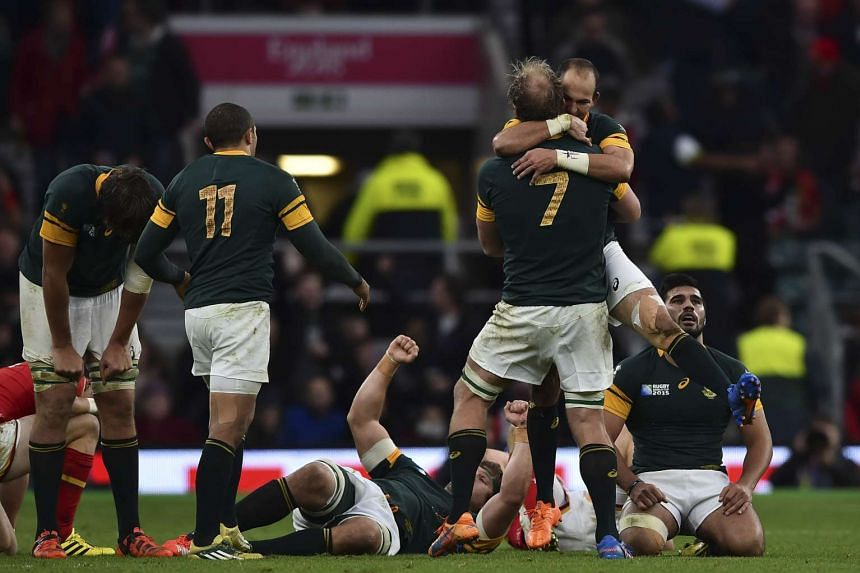 South Africa's scrum half and captain Fourie du Preez (2nd from right) hugs South Africa's flanker Schalk Burger (3rd from right) after winning a quarter final match of the 2015 Rugby World Cup between South Africa and Wales at Twickenham stadium, so