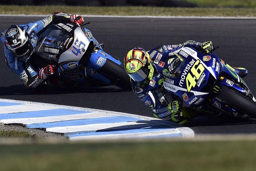 Movistar Yamaha MotoGP rider Valentino Rossi of Italy and GO&FUN Honda Gresini's British rider Scott Redding power through a corner during the qualifying session ahead of the MotoGP Australian Grand Prix at Phillip Island on Oct 17, 2015.