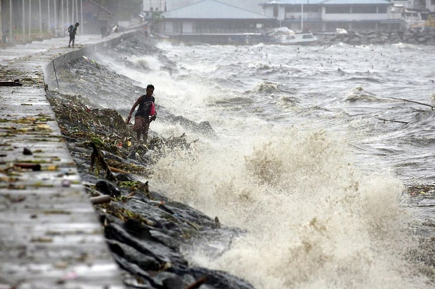 Residents look for recyclable materials amidst waves due to Typhoon Koppu in Manila Bay, on Oct 18, 2015.