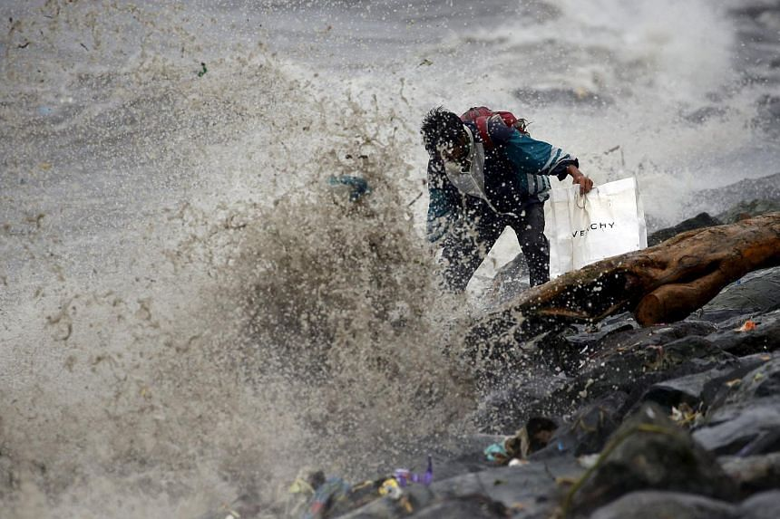 A resident looks for recyclable materials amidst strong waves due to Typhoon Koppu in Manila Bay, on Oct 18, 2015.