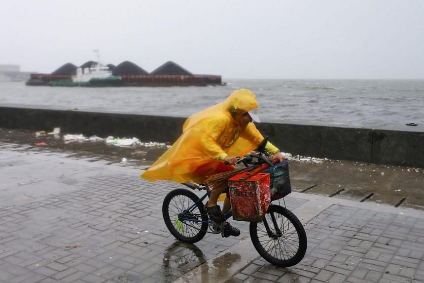 A Filipino rides his bicycle as a shipping barge floats nearby at Manila Bay, Philippines, on Oct 18, 2015.
