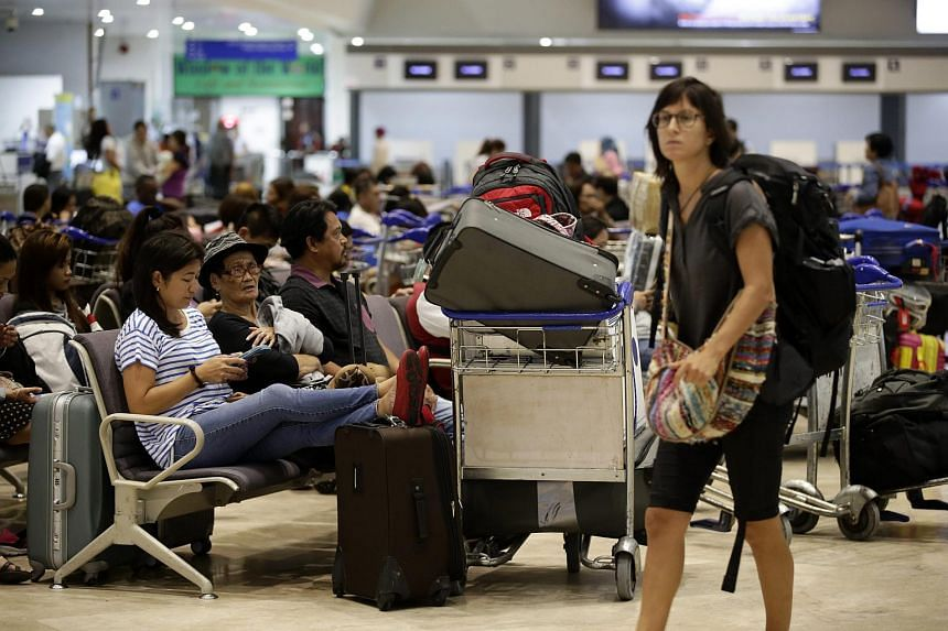 Stranded passengers rest inside the Manila International airport in Pasay city, Philippines, on Oct 18, 2015.