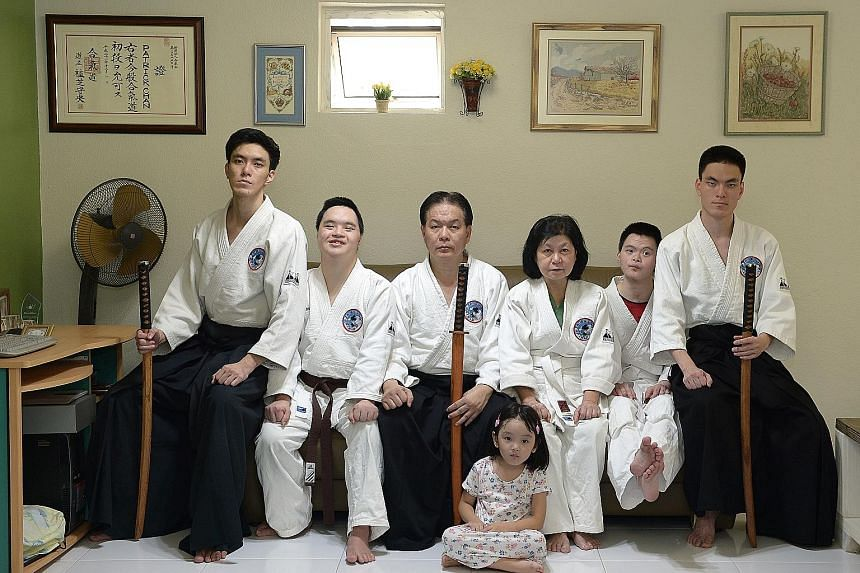 Mr Patrick Chan, 56, (third from left) and his wife Lily Cheok, 63, with their sons (from left) Shamus, 29; Sean, 25; Enoch, 23; and Jonah, 24. Shamus' four-year-old daughter, Cassiel, is sitting on the floor. Aikido is a family affair for the Chans,