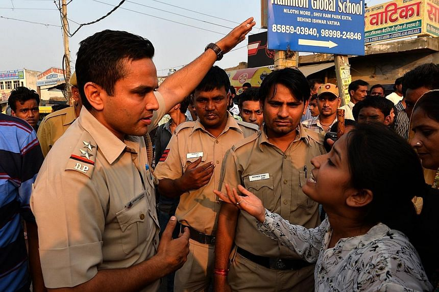 A woman shouting at a policeman during a protest near the home of the toddler who was abducted and raped.