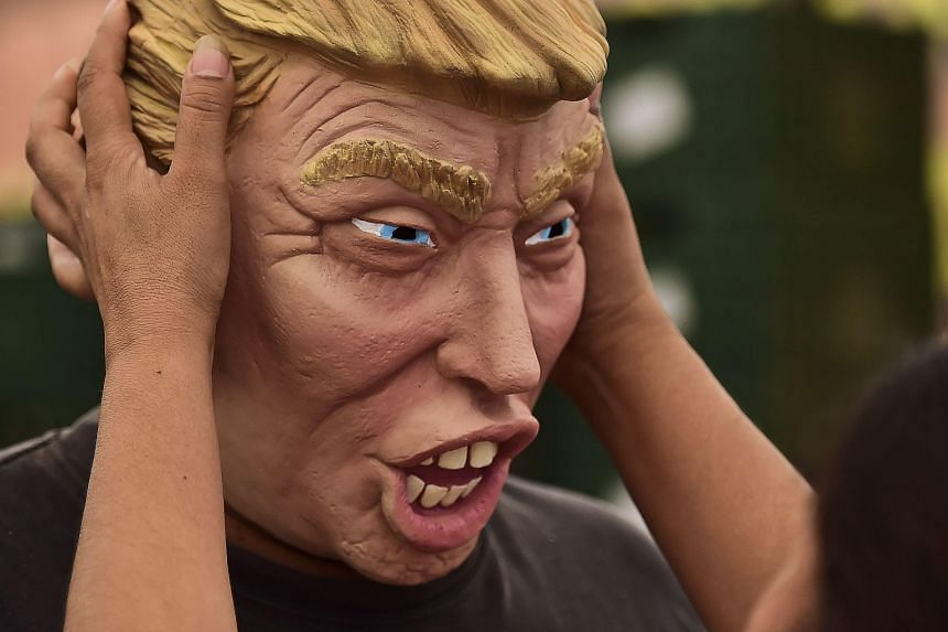 A factory worker checks the production of a Donald Trump mask recently in Mexico. Mr Trump's tendency towards controversial rhetoric has not hurt his ratings so far, with polls of Republican voters showing he leads the 15-candidate field.