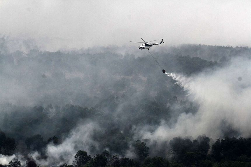 An Indonesian MI-17 helicopter water-bombs a fire spot in the Ogan Komering Ilir area, in South Sumatra province, on Oct 17, 2015.