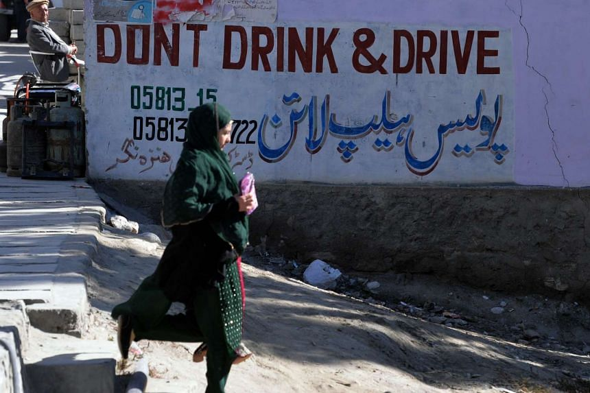 "A woman walks past a sign that says ""Dont Drink and Drive"" along the Karakoram Highway at Aliabad in the Hunza Valley in northern Pakistan, on Sept 29, 2015."