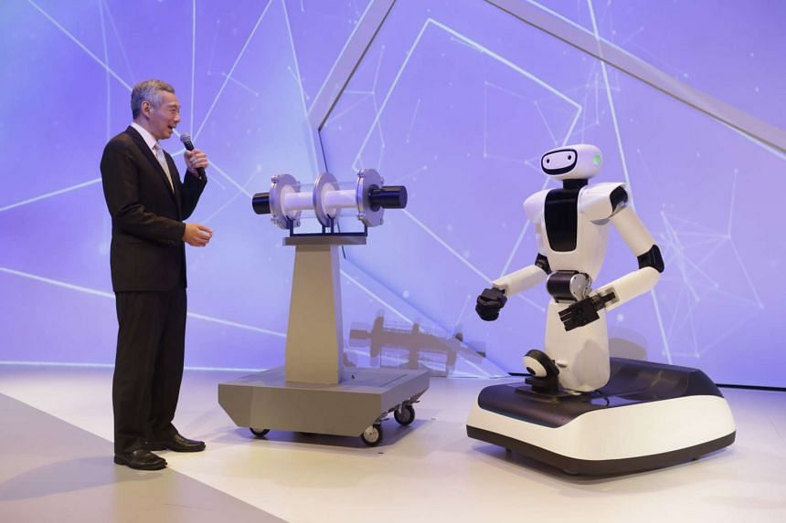 Prime Minister Lee Hsien Loong speaks to Olivia the robot at the opening ceremony for Fusionopolis Two on Oct 19, 2015.