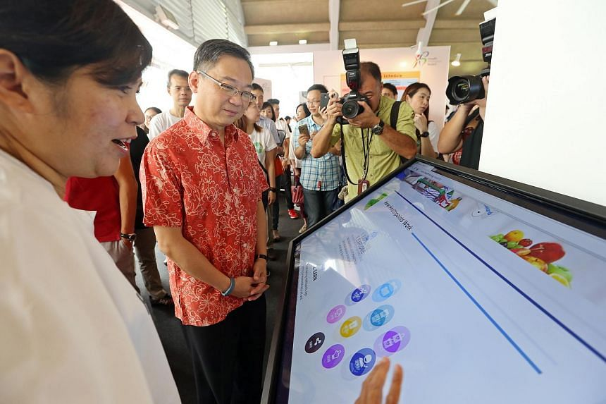 (Left) Anizah Abbas, 45, (Manager, Digital Marketing, Health Promotion Board) shows Health Minister Gan Kim Yong a new app that allows all Singaporeans to access their medical records online.
