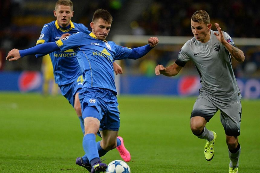 Bate Borisov's Belarusian midfielder Evgeni Yablonski (second left) fights for the ball with Roma's French defender Lucas Digne during the Uefa Champions League group E football match.