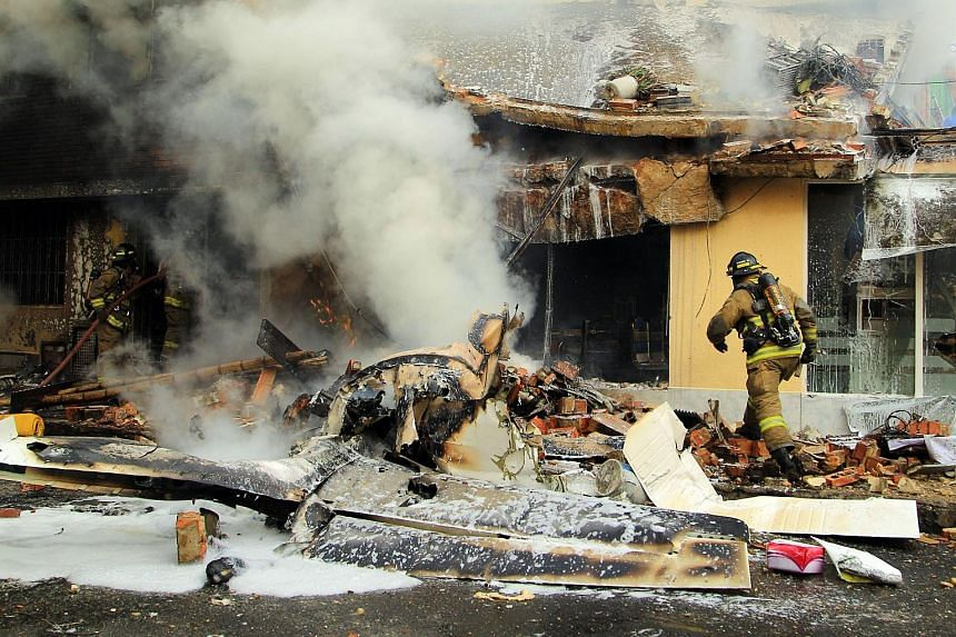 Firefighters put out a fire after a twin-engine plane crashed in a residential area, in Bogota, Colombia, on Oct 18, 2015.
