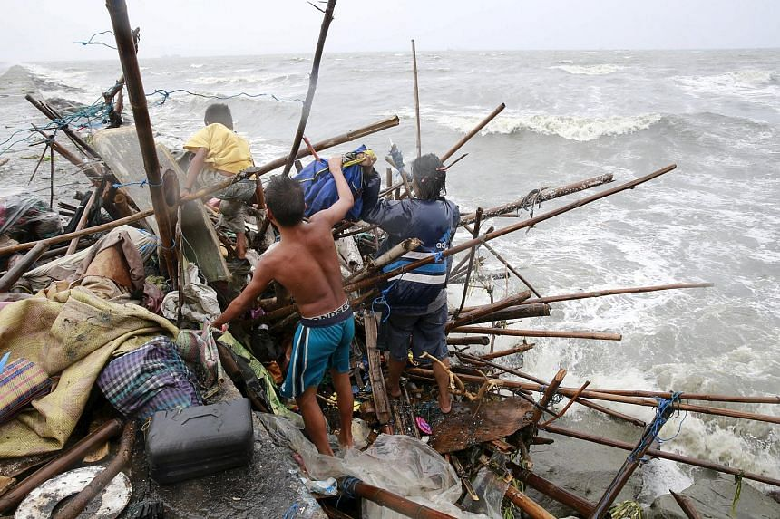 A Taroyo family living along the coast of Manila Bay searches for salvageable items after their house was damaged by strong winds brought by typhoon Koppu.